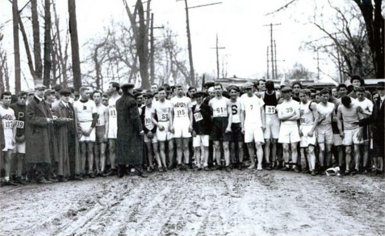 Auf einer schlammigen Straße zwischen kahlen Bäumen warten 123 Männer auf den Start des Boston-Marathons 1912. ©Von Familie Ryan zur Verfügung gestellt