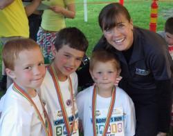 Drei schnelle Teilnehmer des Dick Lytie-Kinderevents feiern ihr Rennen mit Uta. ©Take The Magic Step®