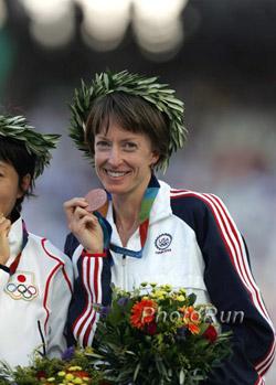 Momentaufnahme – Deena Kastor mit Lorbeerkranz und Bronzemedaille in Athen. © www.photorun.net